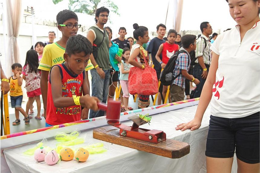 A boy tries out a carnival game at Downtown East. -- ST PHOTO: SEAH KWANG PENG