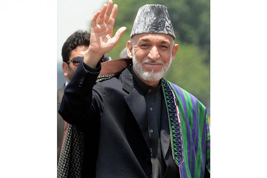 Afghan President Hamid Karzai waves on his arrival at New Delhi airport on May 26, 2014. Mr Karzai is due to step down in the coming weeks after Saturday's run-off election, paving the way for Afghanistan's first democratic transfer of power. -- PHOT