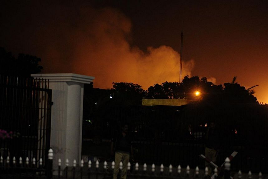 Smoke rises from the burning site of Jinnah International Airport after an assault in Karachi on late June 8, 2014. Heavily armed militants attacked Pakistan's busiest airport in the southern city of Karachi Sunday night. -- PHOTO: AFP