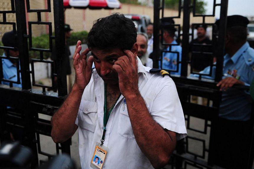 Pakistani airport employees leave the Jinnah International Airport after militants attack in Karachi on June 9, 2014. -- PHOTO: AFP