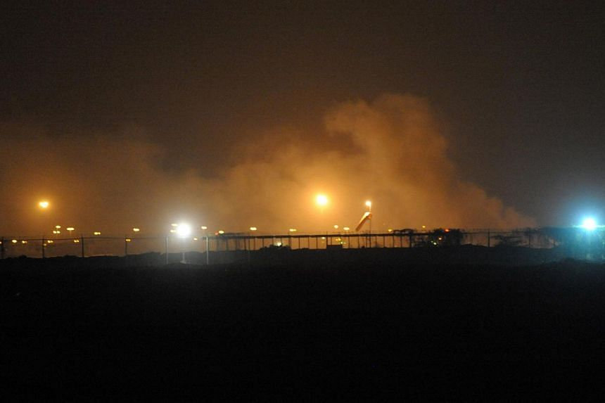 Smoke rises from the Karachi airport terminal after the militants' assault in Karachi on June 9, 2014. -- PHOTO: AFP