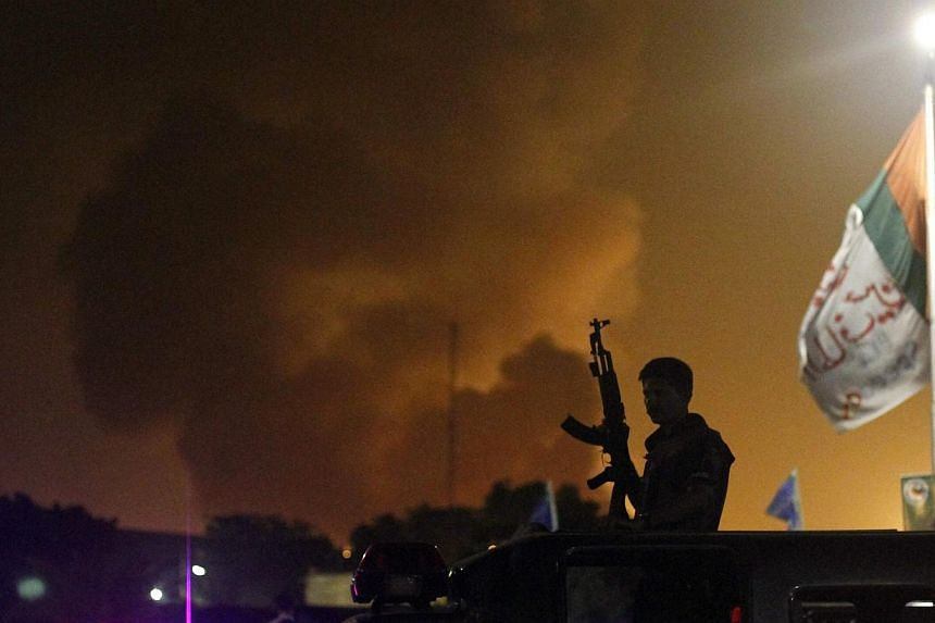 A policeman with a gun stands on a vehicle as smoke bellows from Jinnah International airport in Karachi on June 9, 2014. -- PHOTO: REUTERS