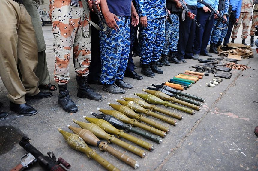 Pakistani policemen show seized weapons after militants attacked Jinnah International Airport in Karachi on June 9, 2014. -- PHOTO: AFP