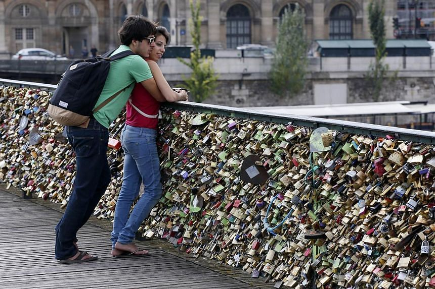 A couple stands on the Pont des Arts in front of padlocks hitched by lovers in Paris on Aug 30, 2013. -- PHOTO: AFP