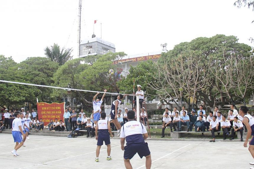 Vietnamese naval servicemen and Filipino naval servicemen play volleyball during a friendly match on Vietnam-held Song Tu Tay or Southwest Cay island of the disputed Spratly Islands on South China Sea on June 8, 2014.China denounced Vietnam and