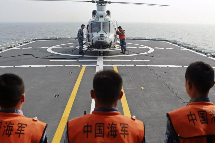 Chinese naval sailors look on as a helicopter gets ready to take off from Chinese naval frigate Linyi during multi-country maritime joint exercises off the coast in Qingdao, Shandong province on April 23, 2014. China has confirmed it will participate