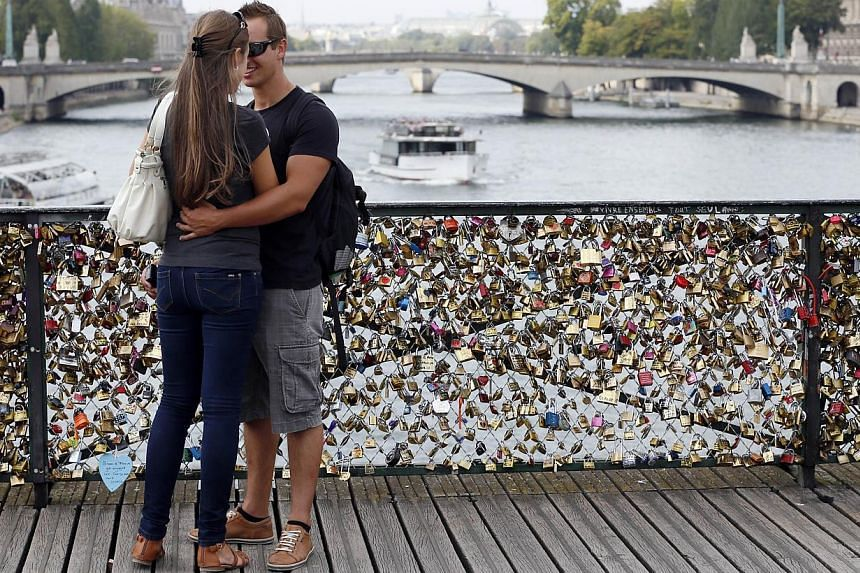 A couple stands on the Pont des Arts in front of padlocks hitched by lovers on August 30, 2013 in Paris. -- PHOTO: AFP