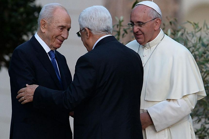 Israeli President Shimon Peres (left) shakes hands with Palestinian leader Mahmud Abbas as Pope Francis looks on after they plant an olive tree in the Vatican's gardens following a joint peace prayer at the Vatican on June 8, 2014. -- PHOTO: AFP