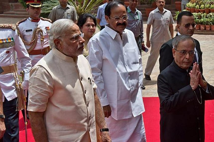 Indian President Pranab Mukherjee (right) gestures a greeting as he arrives with Indian Prime Minster Narendra Modi (left) to address the joint session of Parliament in New Delhi on June 9, 2014.India's new government will engage energetically