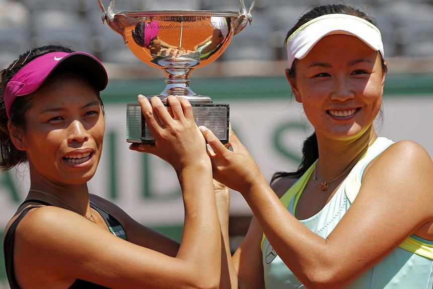 Peng Shuai of China (right) and Hsieh Su-Wei of Taiwan pose with the trophy during the ceremony after winning their women's doubles final match against Sara Errani and Roberta Vinci of Italy at the French Open Tennis tournament at the Roland Garros s