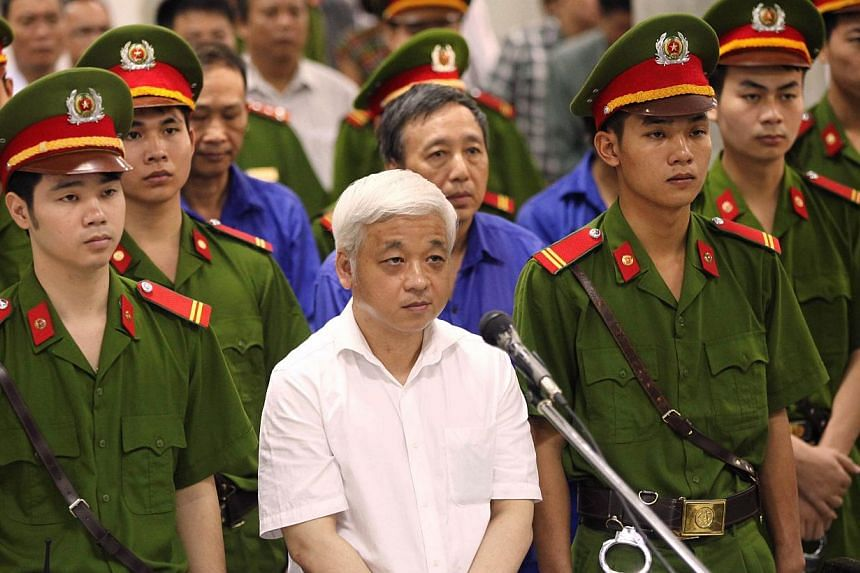Former Vietnamese banking tycoon Nguyen Duc Kien (C), 50, stands listening to the verdict read at the Hanoi People's Court on June 9, 2014.A Vietnamese court on Monday sentenced a disgraced banking tycoon to 30 years in jail over a multi-millio