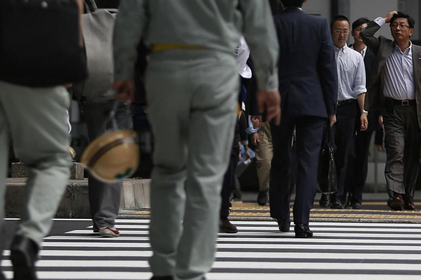 A man scratching his head crosses a street at a business district in Tokyo May 20, 2014. Japan's economy saw its strongest expansion in more than two years during the first quarter of 2013, revised data showed Monday, but a sales tax rise has weighed