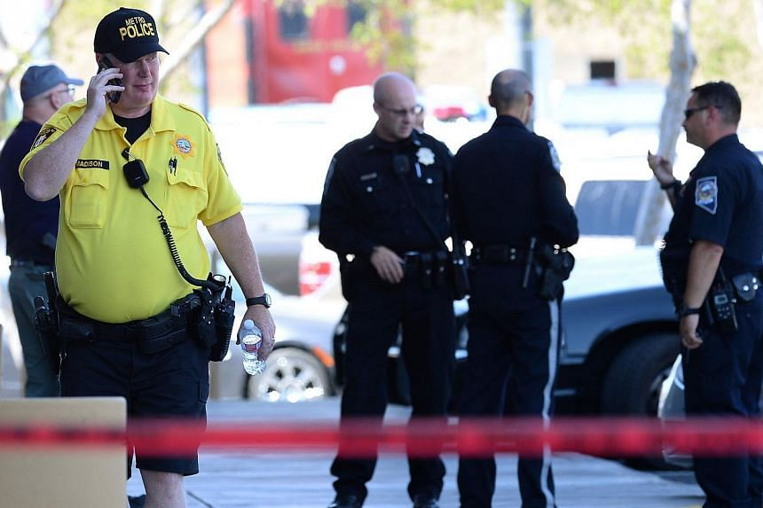 Las Vegas Metropolitan Police Department and Nevada Highway Patrol officers stand near a Wal-Mart on June 8, 2014 in Las Vegas, Nevada.A gun-toting couple who killed two US cops in cold blood saw police as oppressors and may have had anti-gover