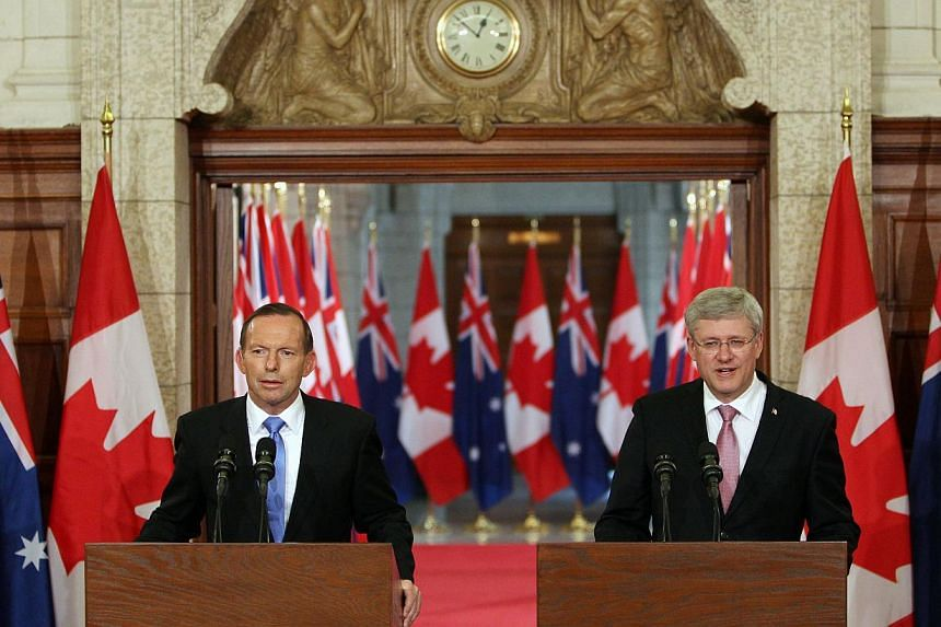 Australian Prime Minister Tony Abbott (left) and Canadian Prime Minister Stephen Harper speak during a joint press conference in Parliament Hill in Ottawa, Canda on June 9, 2014. -- PHOTO: AFP
