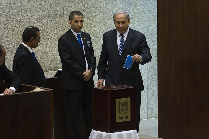 Israel's Prime Minister Benjamin Netanyahu (right) casts his ballot for the presidential election at the Knesset, Israel's Parliament, in Jerusalem on June 10, 2014. Israel's Parliament voted on Tuesday for a new head of state to succeed President Sh