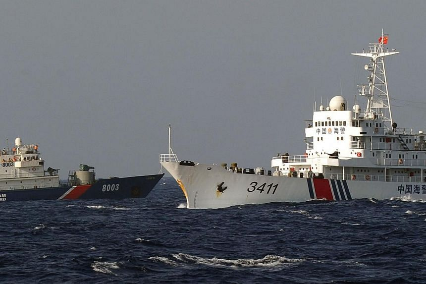 A Vietnamese Coast Guard ship (left) is challenged by a China Coast Guard ship near the site of a Chinese drilling oil rig (right, background) being installed in the disputed waters in the South China Sea off Vietnam's central coast on May 14, 2014.&