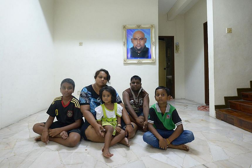Madam Pusparani Mohan, 34, with her children (from left) Dharmaa, 10, Thurgashini, two, Sarveswaran, 11, and Mageswaran, seven. In the background is a portrait of her late husband Chandra Mogan Panjanathan, who was killed after he was hit by a taxi o