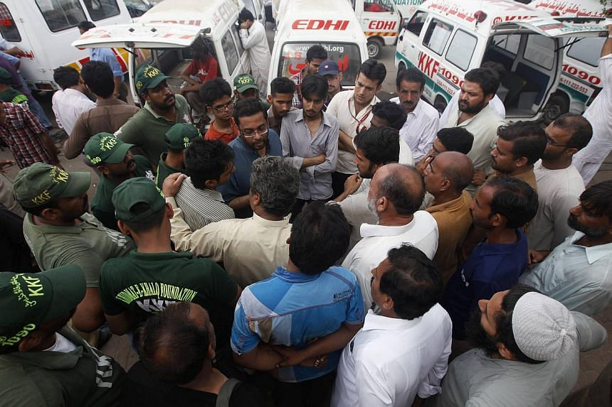 Family members gather to get information and to identify the bodies of victims killed on Sunday's Taleban attack on Jinnah International Airport, outside a hospital morgue in Karachi on June 10, 2014. -- PHOTO: REUTERS