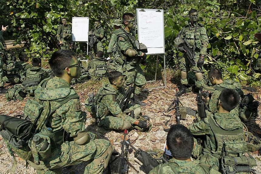 Full-time National Service specialist cadets from Lima Company, Specialist Cadet School, sharing lessons before a training exercise near Pasir Laba Camp, on July 1, 2013. A high-level committee's recommendations to improve NS have been formally accep