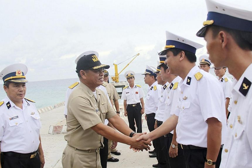 A Filipino naval officer (second from left) being greeted by Vietnamese naval officers upon his arrival on the Vietnam-held Song Tu Tay or South-west Cay island of the disputed Spratly Islands in the South China Sea on June 8, 2014. Vietnamese and Ph