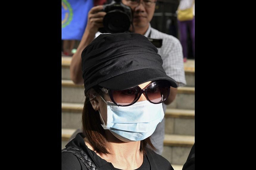 Former beautician Law Wan-tung, 44, leaving a district court in Hong Kong on June 10, 2014. The Hong Kong woman pleaded not guilty on Tuesday to 20 charges of abusing her Indonesian domestic helper in a landmark case, with pictures of her bruised bod