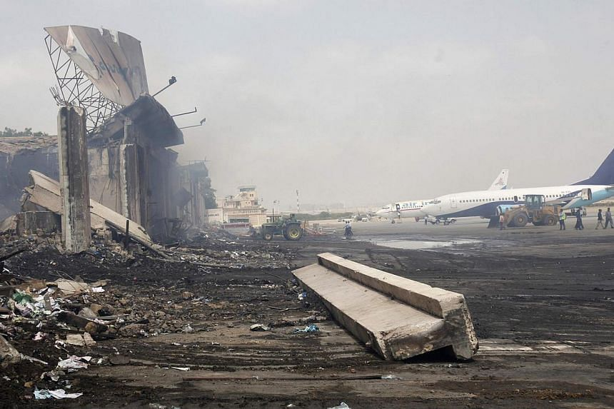 Planes are seen near a section of a damaged building (L) at Jinnah International Airport, after Sunday's attack by Taliban militants, in Karachi on June 10, 2014.Taleban gunmen attacked a security post outside Pakistan's Karachi Airport on Tues