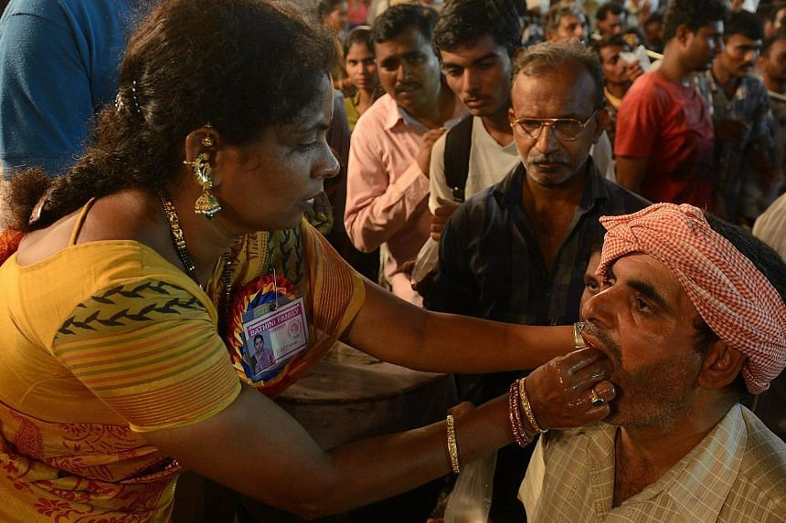 An Indian member of the Bathini Goud family (left) administers 'fish medicine' to a patient at the exhibition grounds in Hyderabad on June 8, 2014. -- PHOTO: AFP