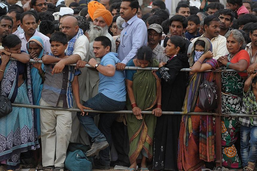 Indian residents wait to receive 'fish medicine' from the Bathini Goud family at the exhibition grounds in Hyderabad on June 8, 2014. -- PHOTO: AFP