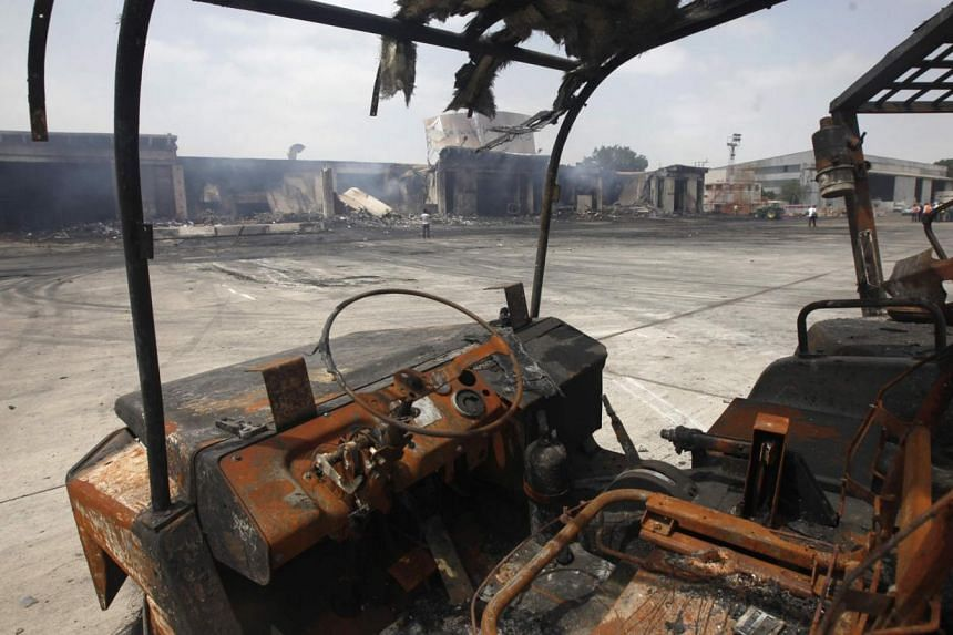 Damaged vehicles are left on the tarmac of Jinnah International Airport, after Sunday's attack by Taleban militants, in Karachi on June 10, 2014. The second attack on Pakistan's Karachi Airport in as many days has ended, a spokesman for the Airp
