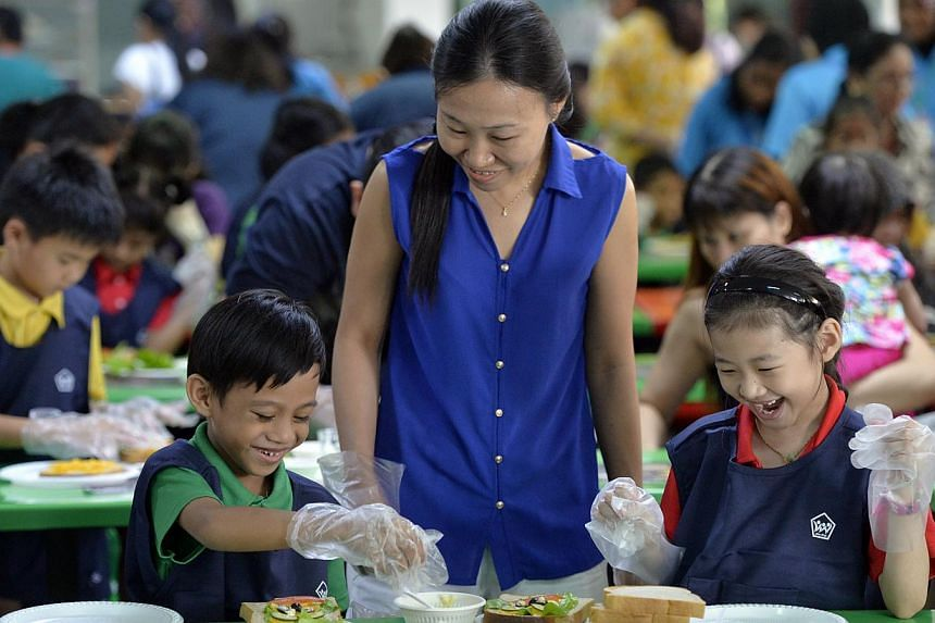 A parent helps Primary 1 students with sandwich making. At least five primary schools have scrapped the parent volunteer scheme which gives parents priority placement when registering their children for Primary 1. -- ST PHOTO: DESMOND FOO