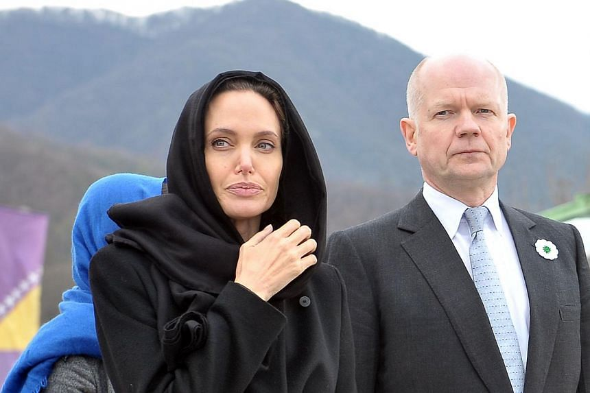 Hollywood actress Angelina Jolie (left) and British Foreign Minister William Hague (right) pay their respects at Srebrenica-Potocari Genocide Memorial cemetery, near Srebrenica, on March 28, 2014.Jolie and Hague will on Tuesday open a four-day