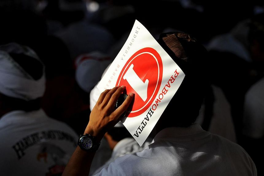 A Balinese supporter holds a poster of Indonesia presidential candidate Prabowo Subianto during their campaign in Denpasar on Bali island on June 6, 2014. -- PHOTO: AFP