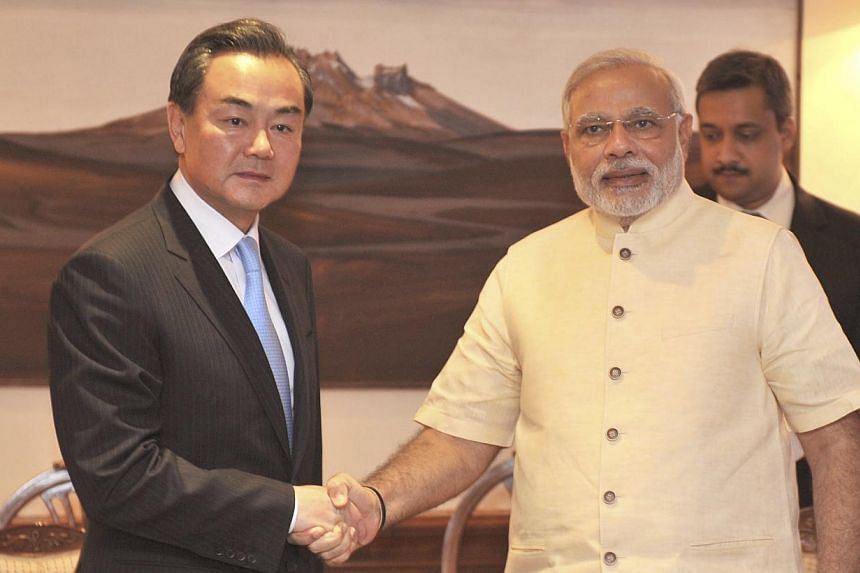 Chinese Foreign Minister Wang Yi (Left) shakes hands with Indian Prime Minister Narendra Modi during their meeting in New Delhi on June 9, 2014. Mr Wang promised on June 8, 2014 to help India's economic development and emphasised that the two countri