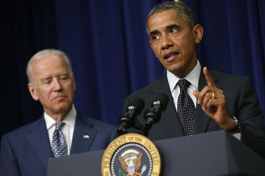"US President Barack Obama (right) speaks as Vice-President Joseph Biden listens during a bill signing ceremony on June 10, 2014. Mr Obama  called for national ""soul searching"" over gun violence, warning that mass shootings were ""off the charts"""