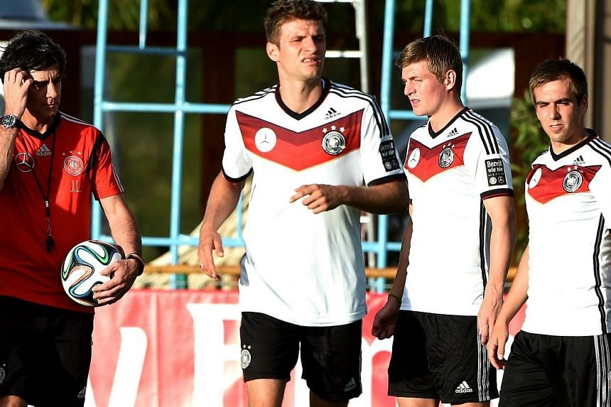 (From left) Germany's coach Joachim Loew stands next to players Thomas Mueller, Toni Kroos and Philipp Lahm during a training session of Germany's national football team in Santo Andre on June 10, 2014. Lahm and Mueller have signed new deals that add