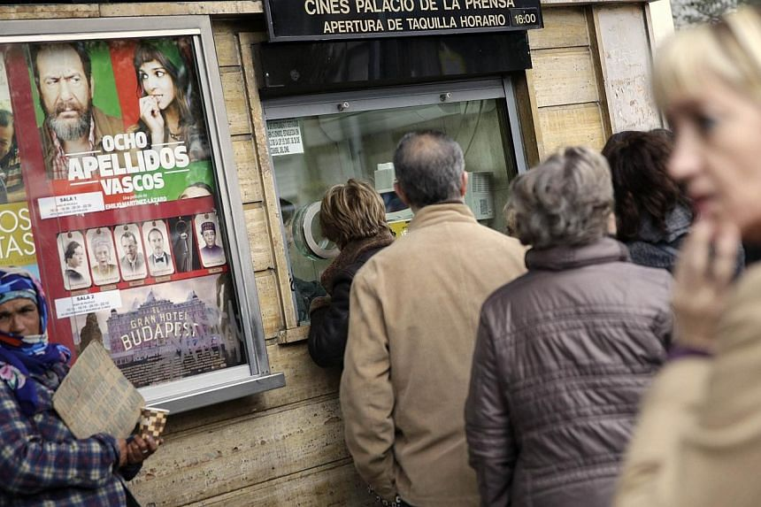 People stand in line to buy tickets for the film 8 Basque Surnames at a cinema in central Madrid on March 30, 2014. -- PHOTO: REUTERS