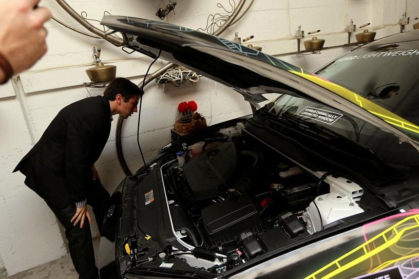Ford Motor Company's Jacob Dylik looks under the hood of a Ford Lightweight Concept car at the TechShop in San Francisco, California June 3, 2014. Auto maker Ford Motor Co is looking to add a new environmental option to its tool box - tomatoes. -- PH