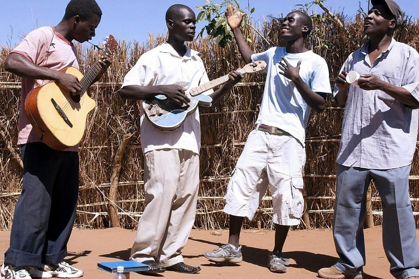 Members of the Malawi Mouse Boys lead vocalist, Zondiwe Kachingwe (left), band leader Nelson Muligo (2nd From left), Alfred Gavana (2nd from right) and backing vocalist Joseph Nekwankwa (right) perform during an interview on May 15, 2014 in the villa