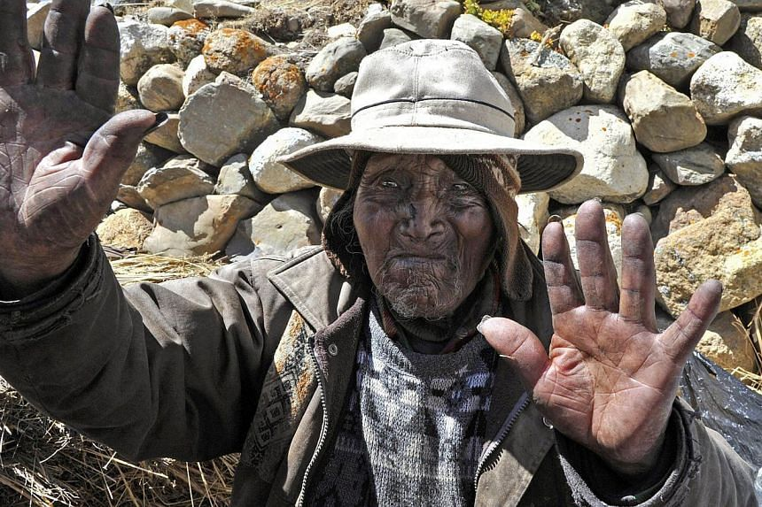 Picture taken on Aug 15, 2013 of Bolivian Carmelo Flores Laura, an Aymara native who claims is 123 years old and if confirmed would be the oldest man alive, waves outside his house in the community of Frasquia, 4050 metres above sea level, on the foo