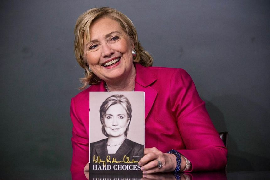 """Former Secretary of State Hillary Clinton poses with her new book, """"Hard Choices"""" during a book signing at a Barnes & Noblein New York Cityon June 10, 2014. -- PHOTO: AFP"""