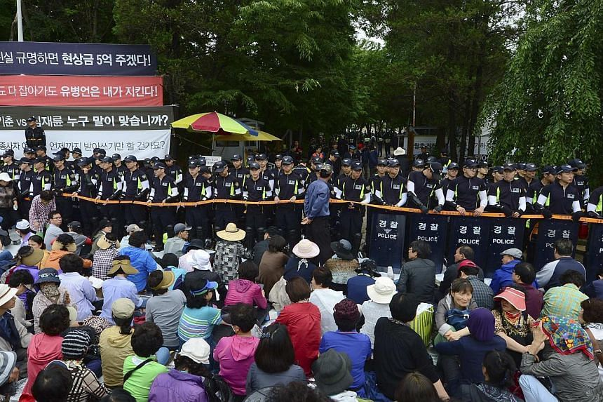 South Korean policemen stand guard in front of the main gate of the Evangelical Baptist Church premises, as church believers sit in front of the police barricade, in Anseong on June 11, 2014. South Korean police raided the religious commune seeking t