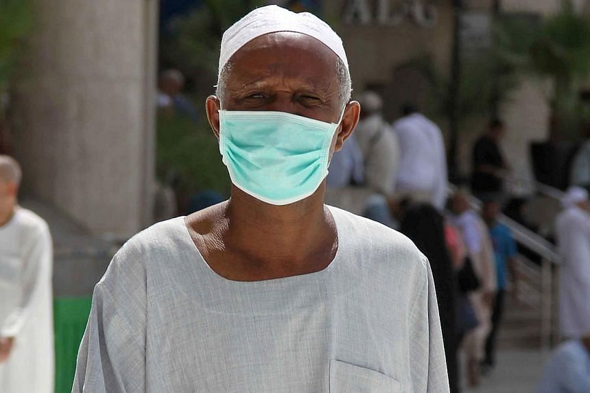 An Asian Muslim pilgrim wears a nose and mouth mask on his way to Islam's holiest shrine, the Kaaba, in the Grand Mosque in the Saudi city of Mecca in Saudi Arabia on May 27, 2014. -- PHOTO: AFP