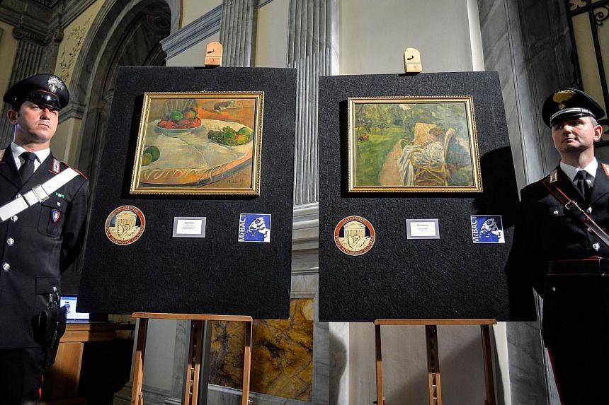 "Carabinieri stand next to the two paintings stolen in London in the 1970s by French artists Paul Gauguin ""Fruits sur une table ou nature au petit chien"", (left) and Pierre Bonnard ""La femme aux deux fauteuils"" on April 2, 2014. -- PHOTO: AFP"