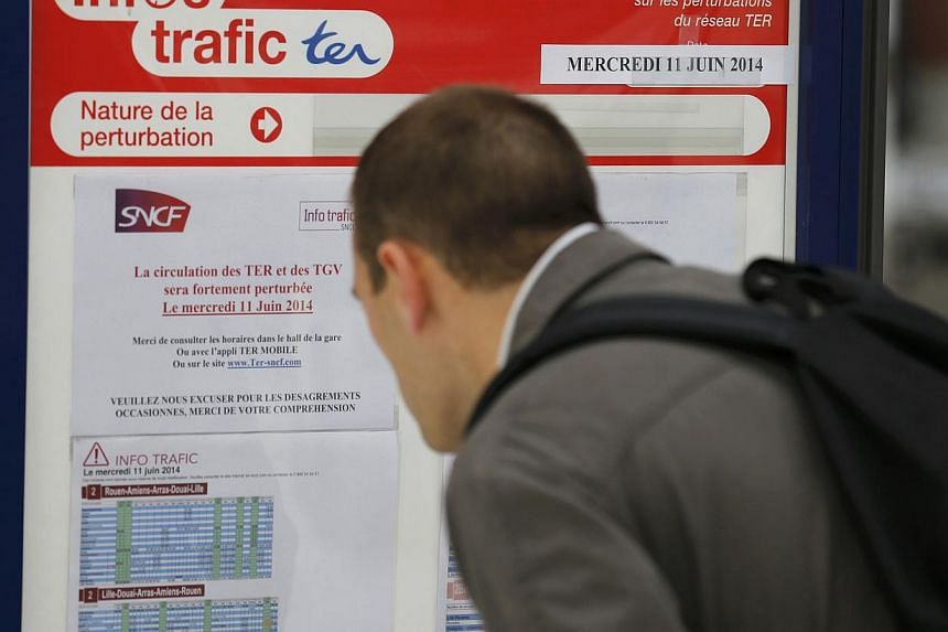 A commuter looks at an information board at the Lille-Flandres station, northern France, June 10, 2014, before the start of a strike by French SNCF railway workers.French commuters faced travel chaos on Wednesday with a major train strike again