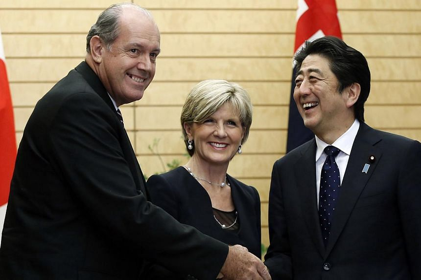 Australian Defence Minister David Johnston (left) and Australia's Foreign Minister Julie Bishop (centre) shake hands with Japan's Prime Minister Shinzo Abe at Mr Abe's official residence in Tokyo on June 11, 2014. -- PHOTO: REUTERS