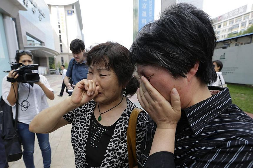 A woman (left), whose son, daughter-in-law and grandson were aboard the missing Malaysia Airlines flight MH370, cries after she and other family members failed to express their appeals to the airline outside its office in Beijing on June 11, 2014.&nb