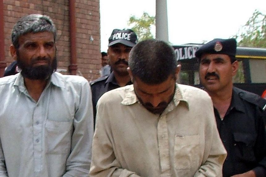 Pakistani police officers escort brothers Mohammad Arif (second, right) and Farman Ali (second, left), suspected of cannibalism, to a local court in Sargodha on April 15, 2014. -- PHOTO: AFP