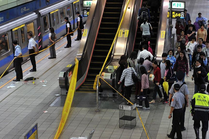 Police blockade the scene of a stabbing incident at the Jiangzicui Station of the Taipei Metro in Taipei on May 21, 2014.A Taiwanese man was arrested on Wednesday for threatening public order after allegedly setting up multiple Facebook fan pag