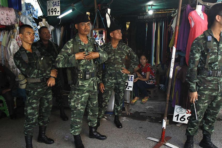 """Soldiers stand guard at a shop at Chatuchak market in Bangkok on June 8, 2014.Thailand's military junta is giving away movie tickets this weekend to promote """"love and harmony"""", a spokesman for the junta said on Wednesday, in its latest effort t"""