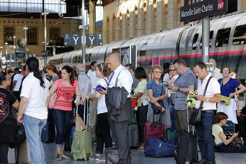 Commuters wait for a train during a nationwide strike by French SNCF railway workers at Marseille train station, June 12, 2014.Half of scheduled train journeys across France were cancelled on Thursday in the second day of a strike against a pla